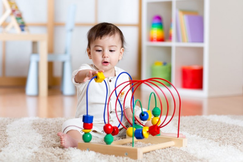 54307007 - toddler girl playing with colorful toy in nursery room